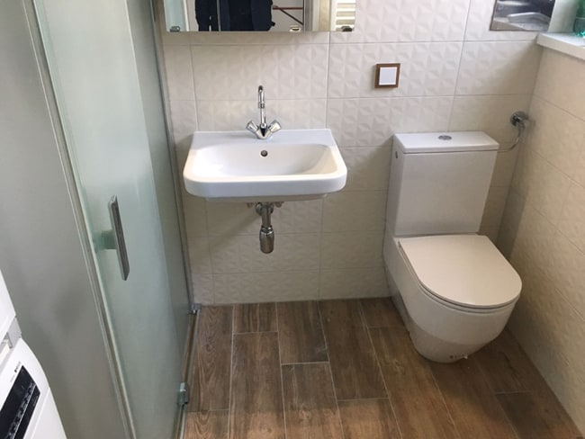 Kleines Bad mit WC, Waschbecken und Dusche